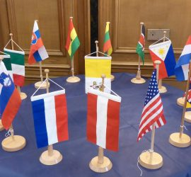 Flags of Apostolat Militaire International on a table
